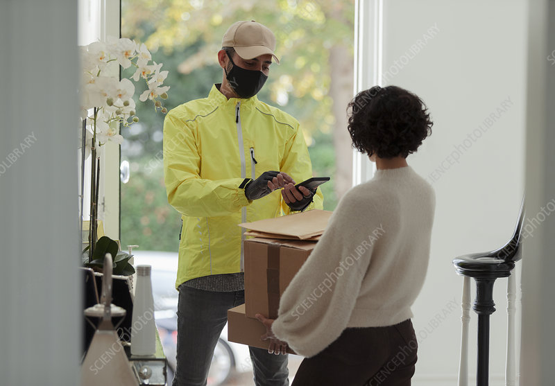 Woman receiving package from delivery man in face mask