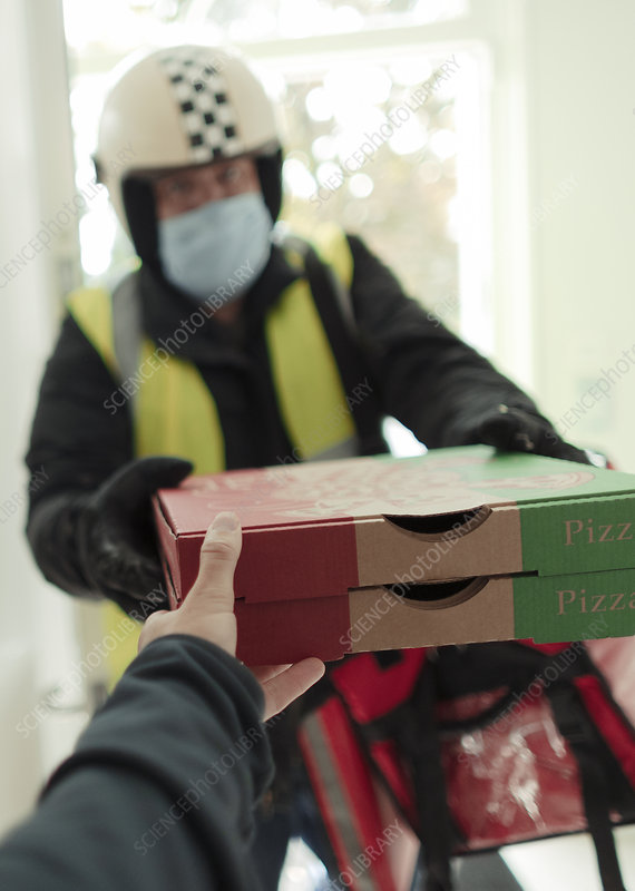 Man in face mask and helmet delivering pizza