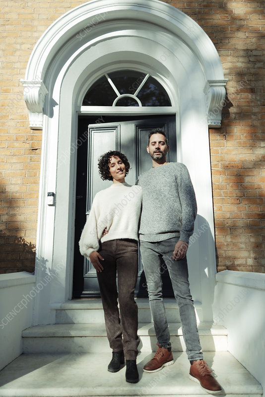 Portrait couple at arched front door on house stoop