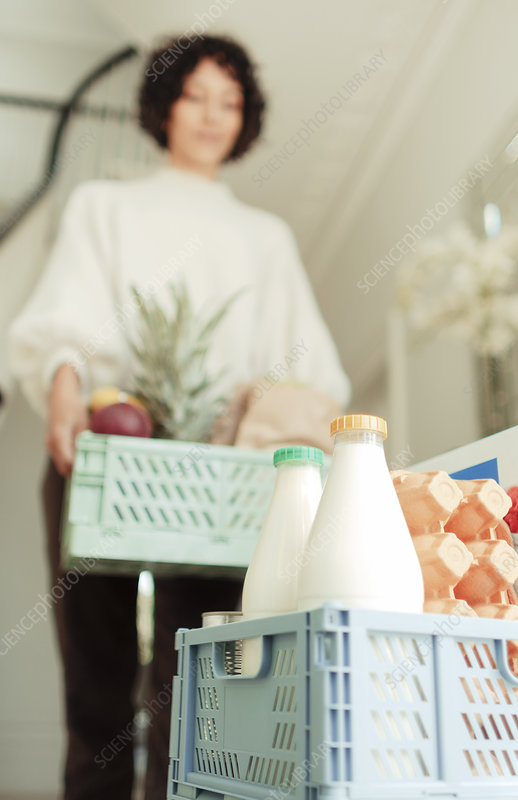 Woman receiving grocery delivery at home