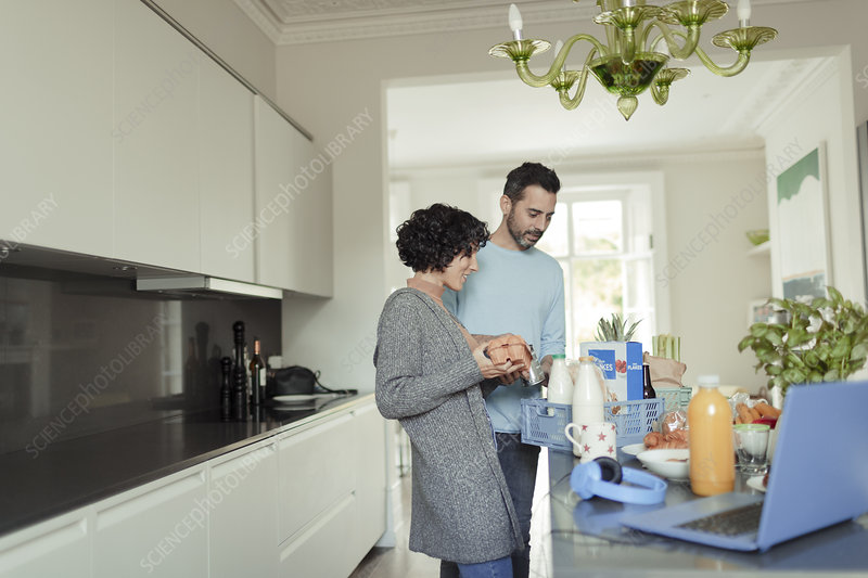 Couple unloading grocery delivery at kitchen counter