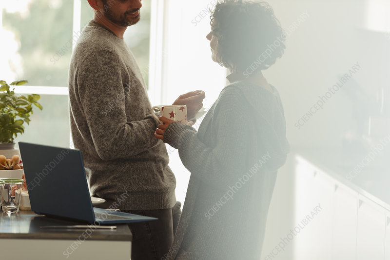 Couple talking at laptop in morning kitchen