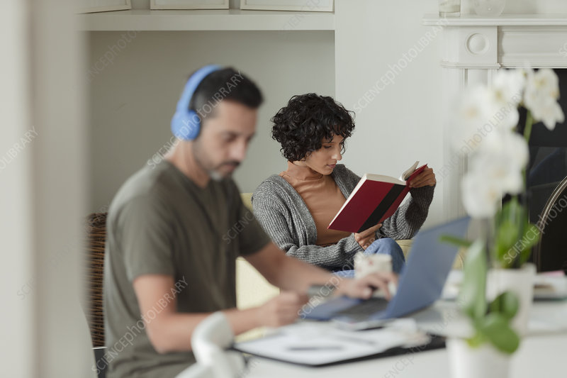Couple reading and working from home at laptop