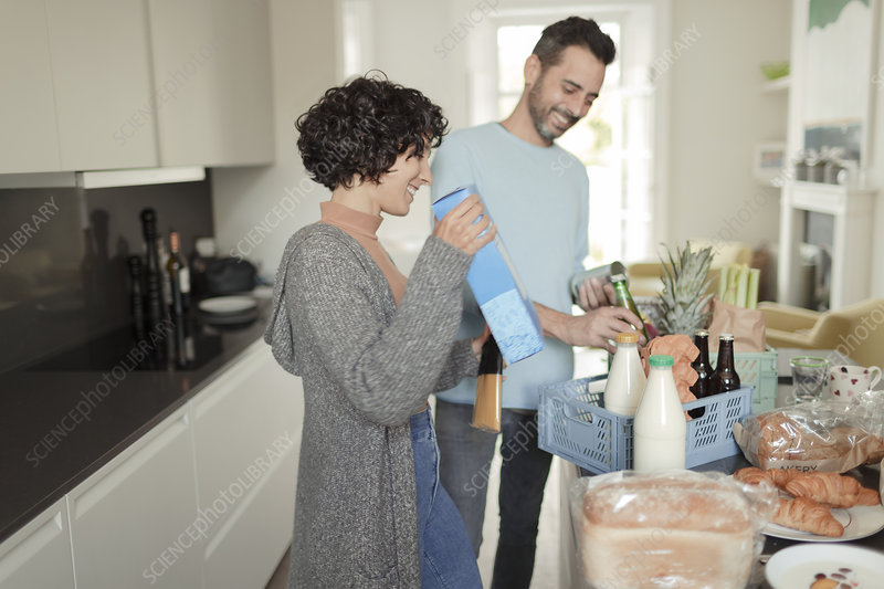 Happy couple unpacking grocery delivery at kitchen counter