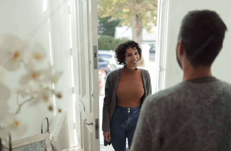 Husband greeting smiling wife at front door