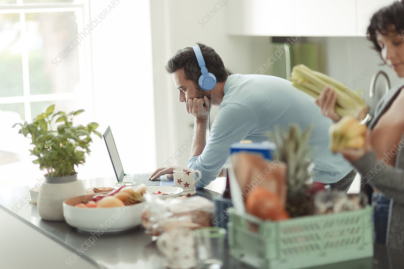 Man with headphones working from home at laptop