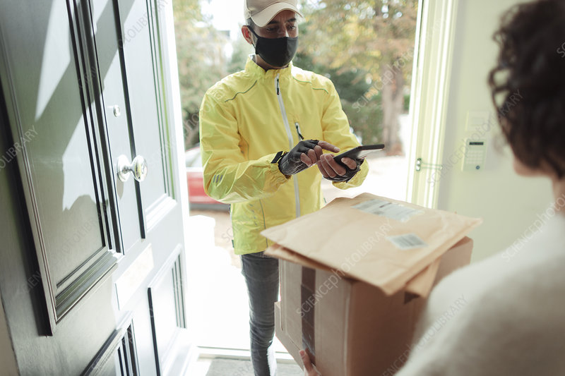 Woman receiving packages from delivery man in face mask