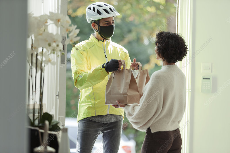 Woman receiving food delivery from man in face mask
