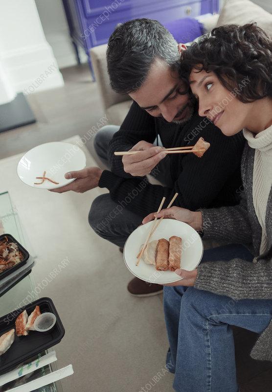 Playful husband feeding egg roll to wife with chopsticks
