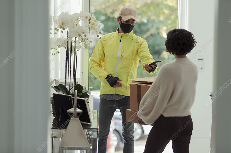Courier in face mask delivering packages to woman at home