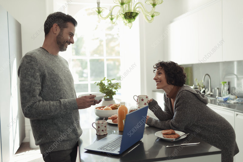 Happy couple enjoying breakfast and working at laptop