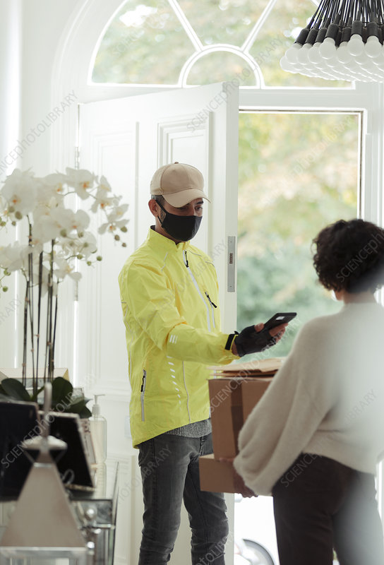 Courier in face mask delivery packages to woman at home