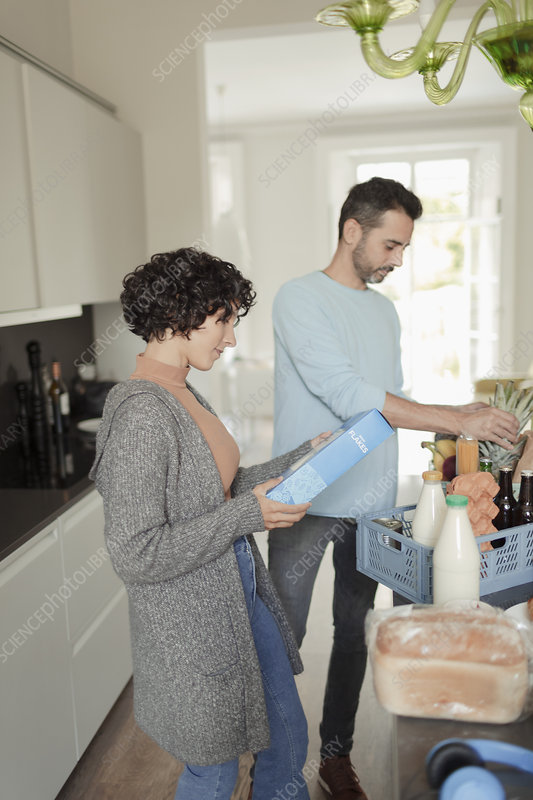 Couple unloading groceries in kitchen
