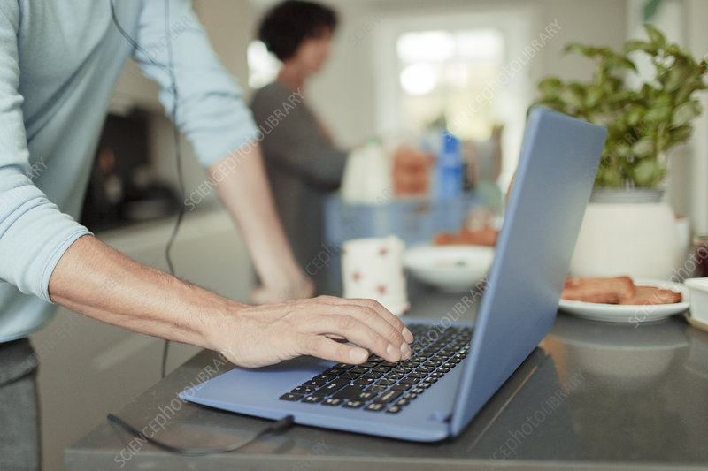 Man working from home at laptop on kitchen counter