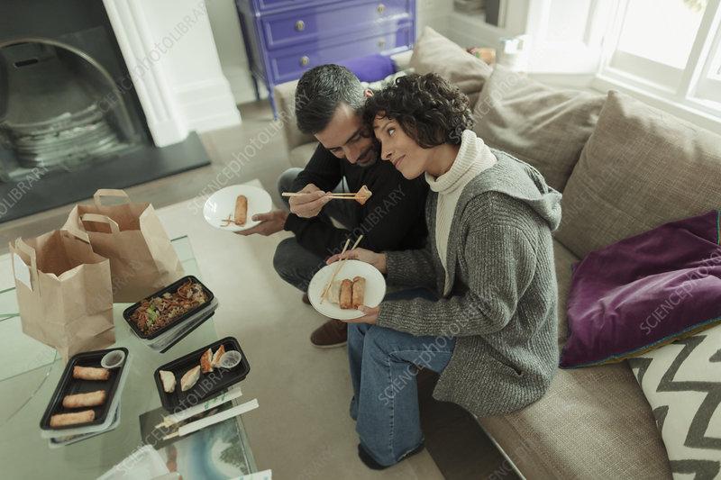 Couple enjoying takeout food with chopsticks on sofa