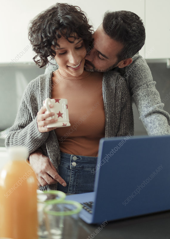 Husband kissing wife working from home at laptop