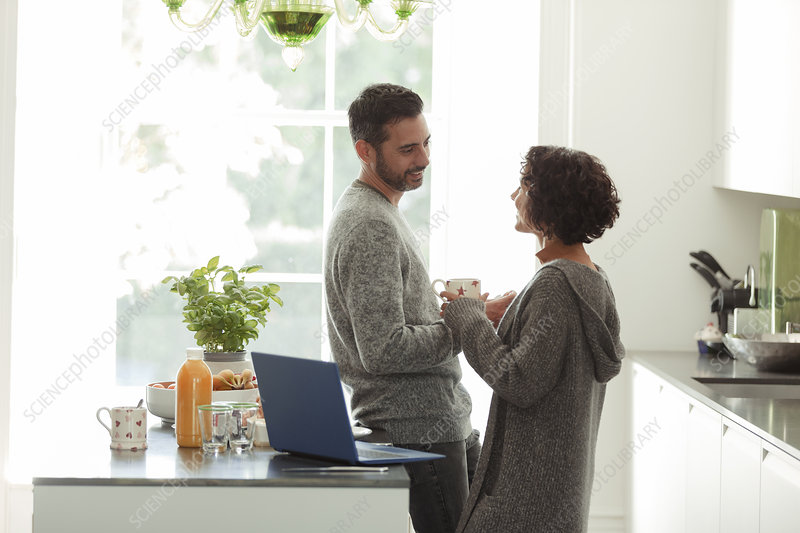 Happy couple talking and working in morning kitchen