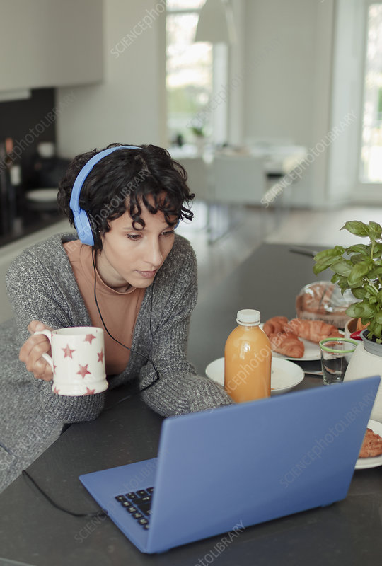 Woman with headphones working from home at laptop