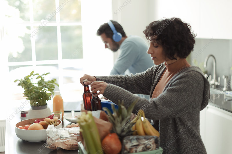 Woman unloading groceries while husband works at laptop