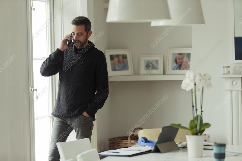 Man working from home talking on smart phone at window