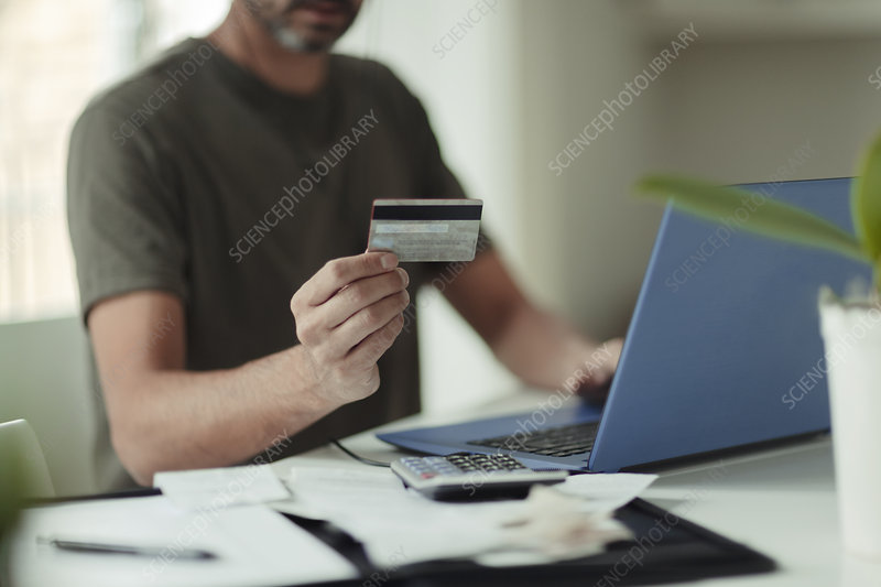 Man with credit card online shopping at laptop