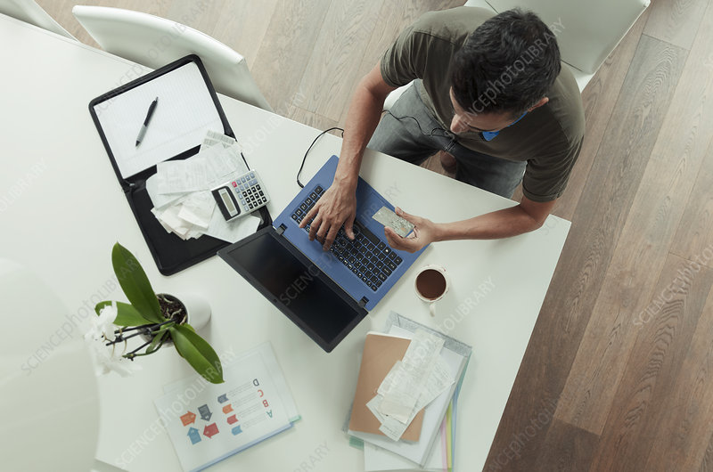 Man with credit card paying bills at laptop