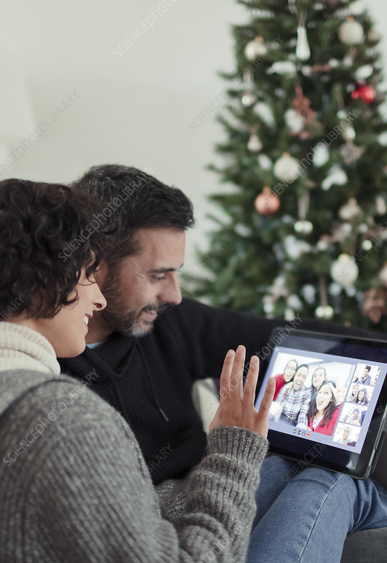 Happy couple video chatting with family at Christmas