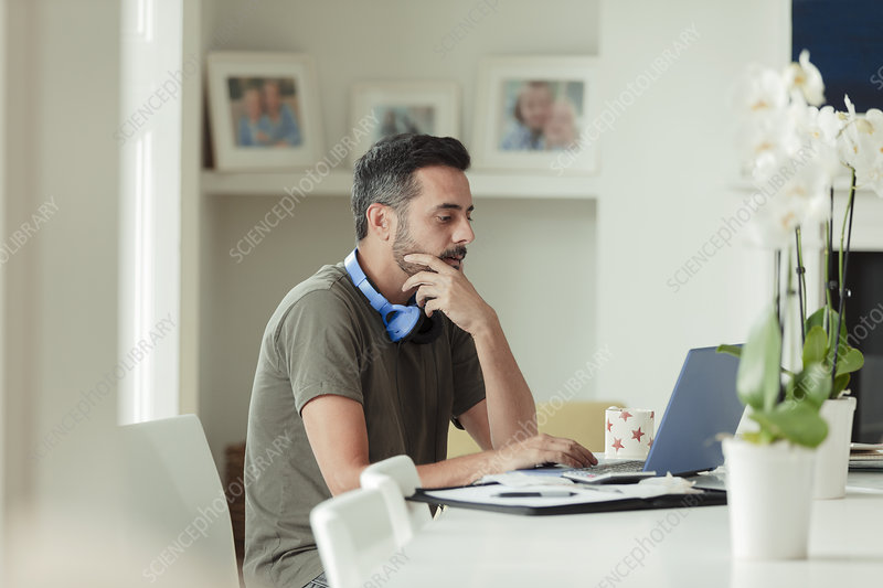 Man working from home at laptop on dining table
