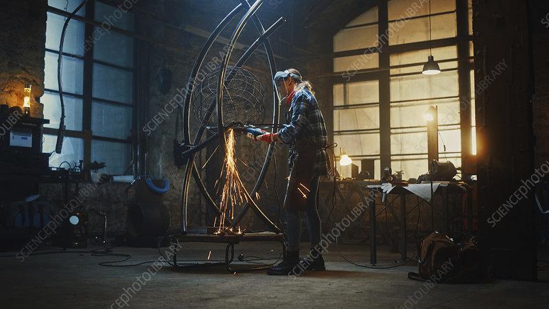 Sculptor walks up to a metal tube sculpture