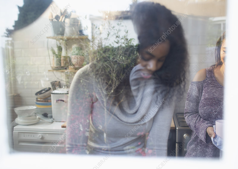 Mother and daughter at kitchen window
