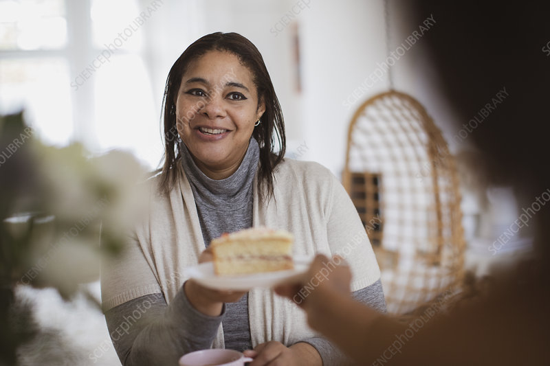 Daughter serving slice of cake to mother