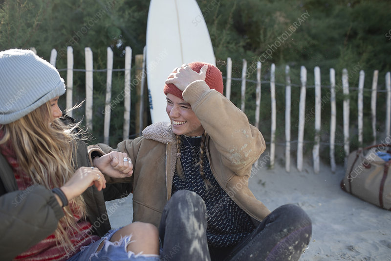 Happy young friends laughing on beach