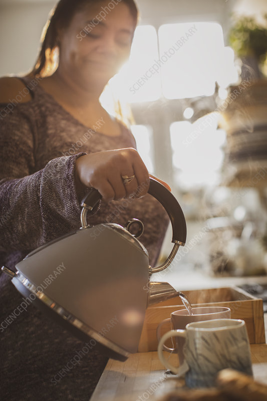 Woman with teapot pouring hot tea into mugs