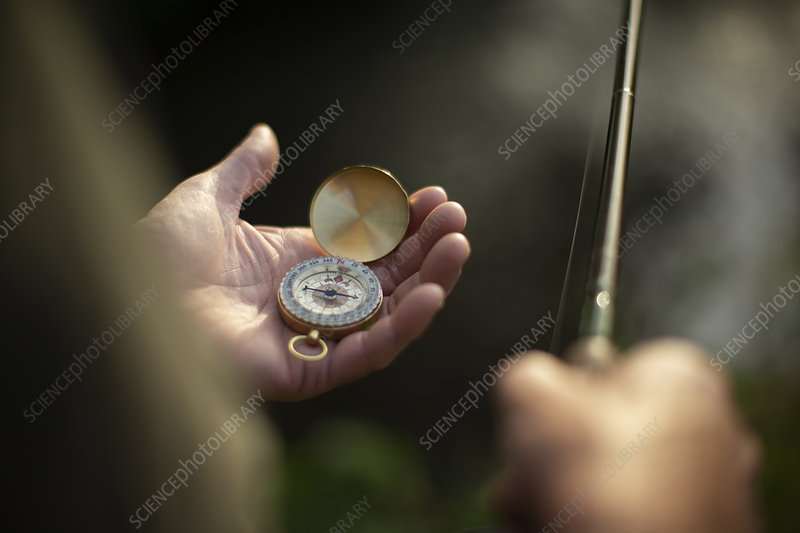 Close-up of a man holding fishing pole and compass