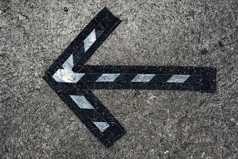 Black and white arrow symbol on asphalt ground