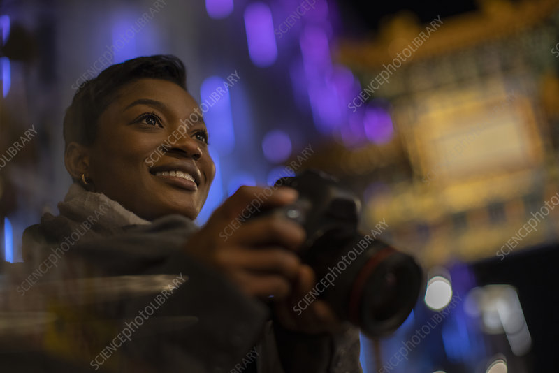 Happy young woman with camera in city at night