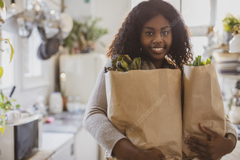 Young woman with groceries in kitchen