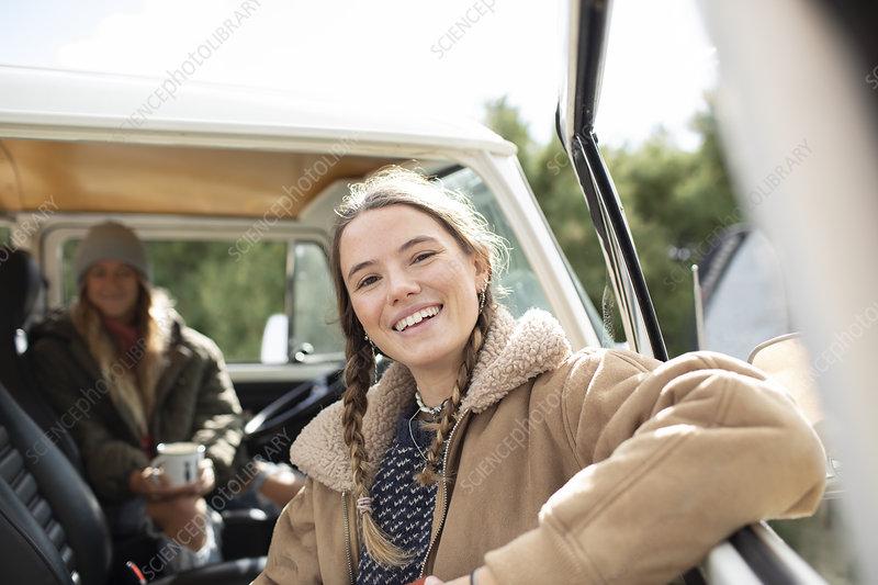 Happy young woman in sunny van doorway
