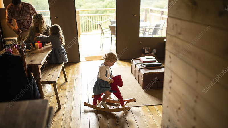 Girl playing on rocking horse in wood cabin