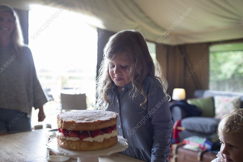 Girl looking at strawberry cake in yurt cabin