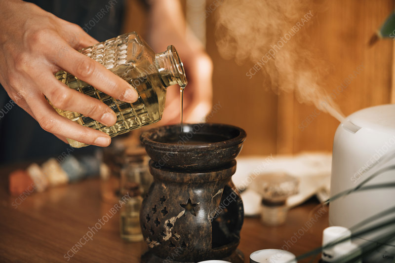 Pouring aromatic oil into an essential oil diffuser