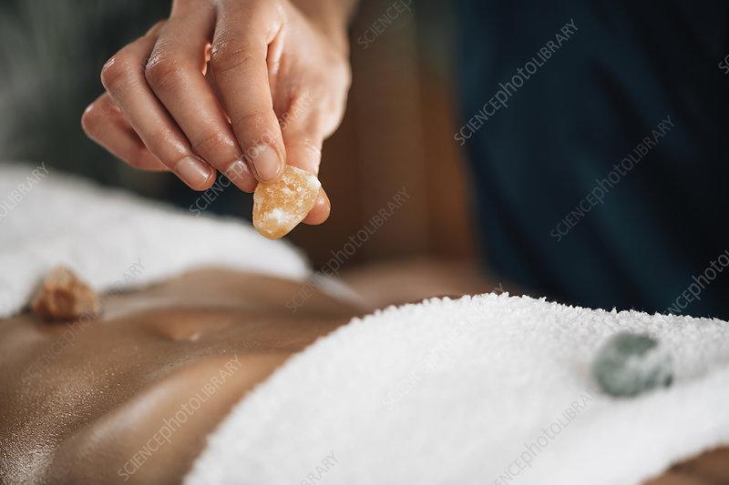 Ayurvedic practitioner using crystals for chakra healing