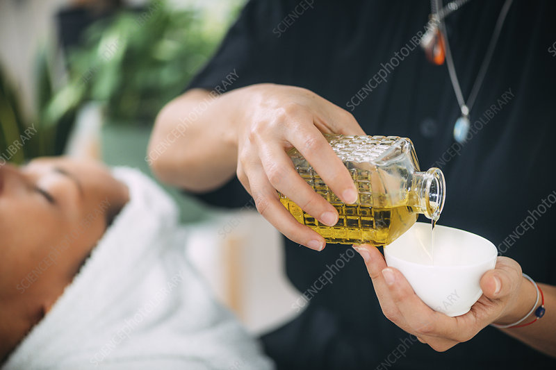 Pouring ethereal ayurvedic oil into a bowl