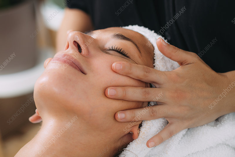 Ayurveda therapist massaging female client face