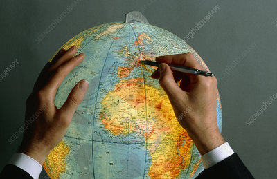 Man pointing to a position on a globe with a pen