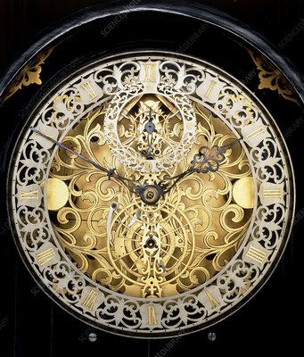 Face of an antique skeleton clock, showing gearing