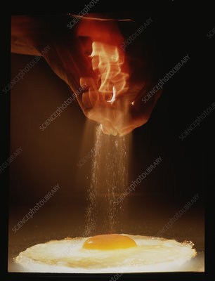 Sprinkling salt onto a fried egg