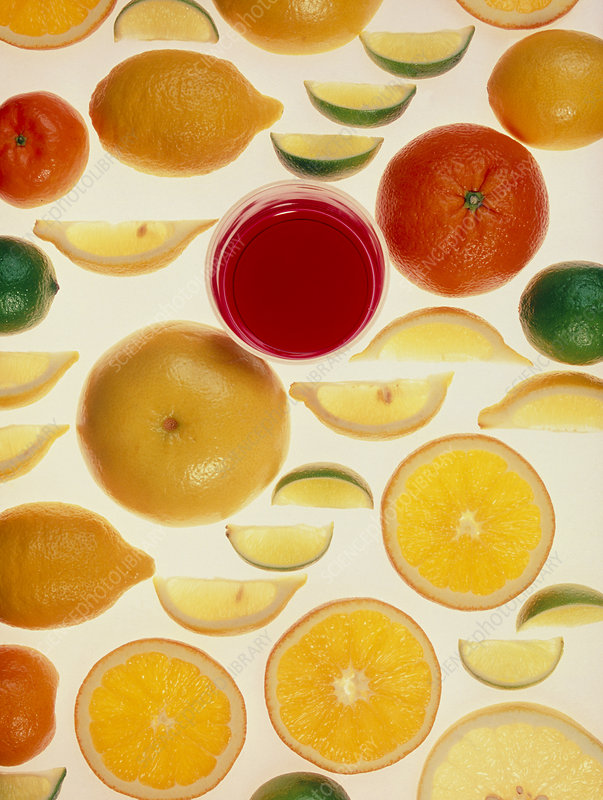 Slices of various citrus fruits and glass of juice
