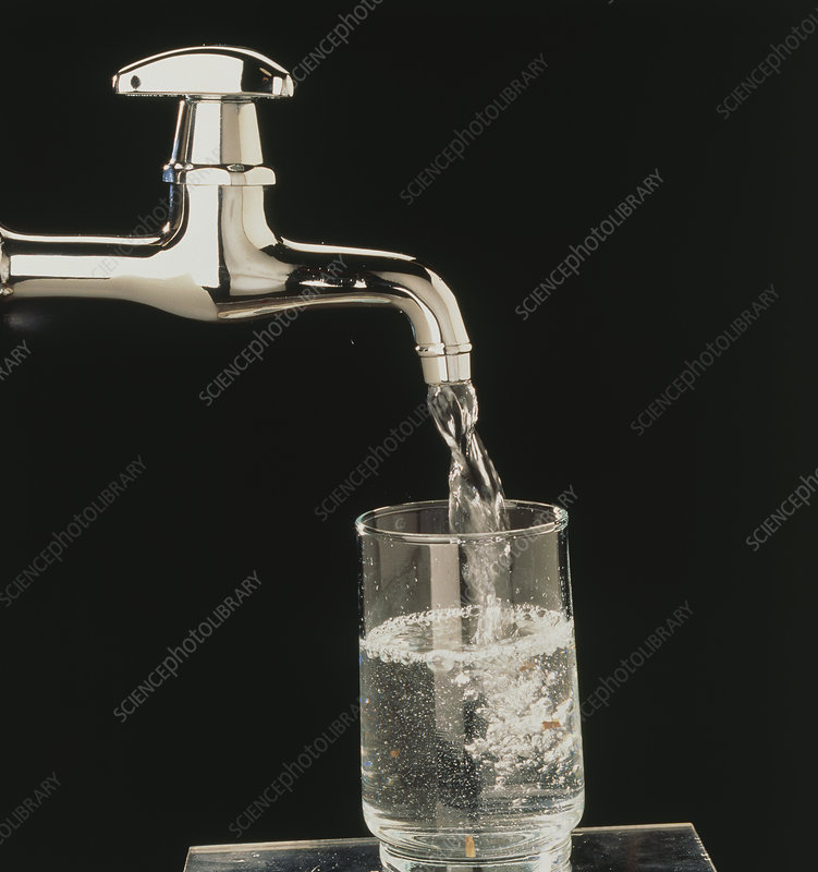 Household tap pouring drinking water into a glass