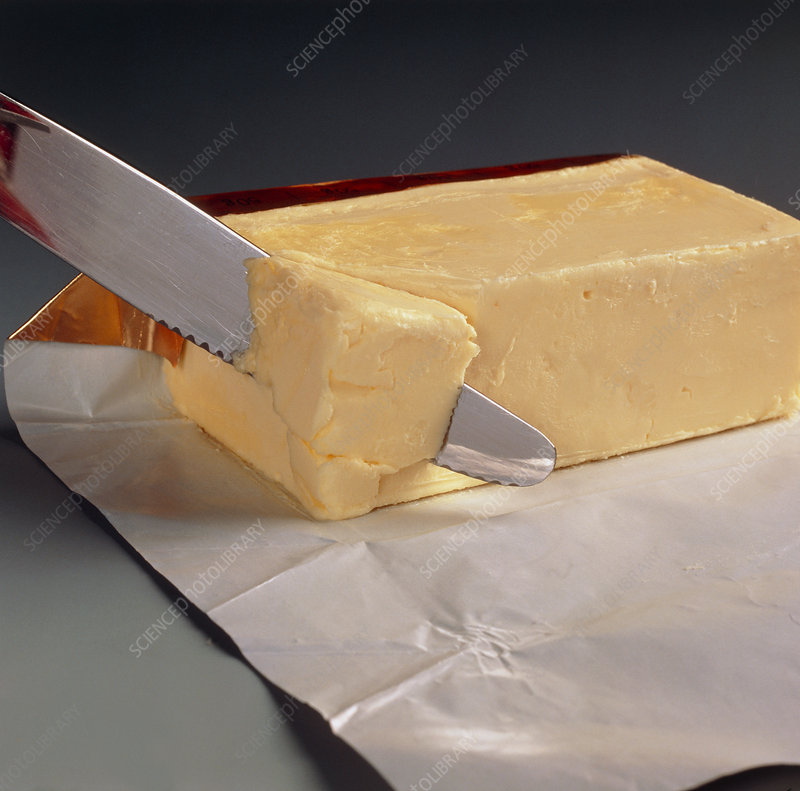 Block of butter being cut with a knife